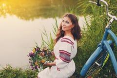 Νέα γυναίκα στο εθνικό ουκρανικό λαϊκό κοστούμι με το ποδήλατο Στοκ εικόνες με δικαίωμα ελεύθερης χρήσης
