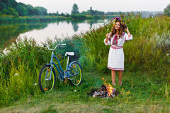 Νέα γυναίκα στο εθνικό ουκρανικό λαϊκό κοστούμι με το ποδήλατο Στοκ Εικόνες