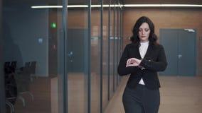 Νέα γυναίκα στο επιχειρησιακό κοστούμι που περπατά κάτω από το διάδρομο ενός κτιρίου γραφείων απόθεμα βίντεο