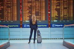 Νέα γυναίκα στο διεθνή αερολιμένα που εξετάζει τον πίνακα πληροφοριών πτήσης, που ελέγχει την πτήση της στοκ φωτογραφία