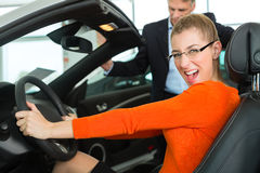 Νέα γυναίκα στο κάθισμα του αυτοκινήτου στη εμπορία αυτοκινήτων Στοκ Εικόνες