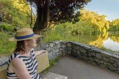 Νέα γυναίκα στο καπέλο και το ριγωτό φόρεμα που κοιτάζει στη λίμνη στη θερινή ημέρα στοκ φωτογραφία με δικαίωμα ελεύθερης χρήσης