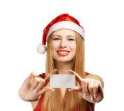 Νέα γυναίκα στο καπέλο Άγιου Βασίλη με τη ευχετήρια κάρτα Χριστουγέννων Στοκ Φωτογραφία