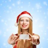 Νέα γυναίκα στο καπέλο Άγιου Βασίλη με τη ευχετήρια κάρτα Χριστουγέννων Στοκ φωτογραφίες με δικαίωμα ελεύθερης χρήσης