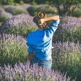 Νέα γυναίκα στο καπέλο αχύρου που απολαμβάνει lavender τον τομέα, τετραγωνική συγκομιδή Στοκ Φωτογραφίες