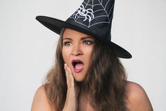 Νέα γυναίκα στο καπέλο μαγισσών αποκριών με το έκπληκτο πρόσωπο Στοκ φωτογραφίες με δικαίωμα ελεύθερης χρήσης