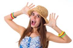 Νέα γυναίκα στο καπέλο που κάνει τα πρόσωπα Στοκ Εικόνες