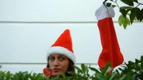 Νέα γυναίκα στο καπέλο του santa που κοιτάζει γύρω για κάποιο απόθεμα βίντεο