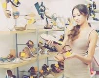 Νέα γυναίκα στο κατάστημα παπουτσιών στοκ εικόνα με δικαίωμα ελεύθερης χρήσης
