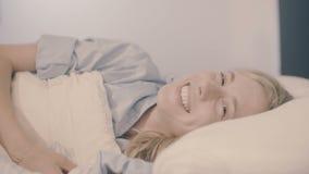 Νέα γυναίκα στο κρεβάτι που ξυπνά επάνω να χαμογελάσει και που τεντώνει την εξέταση τη κάμερα απόθεμα βίντεο