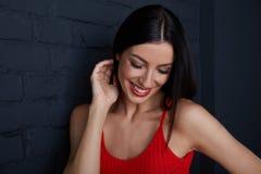 Νέα γυναίκα στο κόκκινο γέλιο ενάντια στο μαύρο τοίχο Στοκ Φωτογραφία