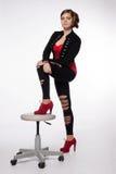 Νέα γυναίκα στο κόκκινο πουκάμισο, σύγχρονο σακάκι, περικνημίδες με τις τρύπες, σχετικά με Στοκ Εικόνες