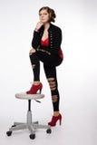 Νέα γυναίκα στο κόκκινο πουκάμισο, σύγχρονο σακάκι, περικνημίδες με τις τρύπες, σχετικά με Στοκ Φωτογραφίες