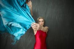 Νέα γυναίκα στο κόκκινο unitard που κυματίζει ένα μπλε μαντίλι Στοκ Εικόνες