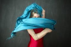 Νέα γυναίκα στο κόκκινο unitard που κυματίζει ένα μπλε μαντίλι Στοκ φωτογραφία με δικαίωμα ελεύθερης χρήσης