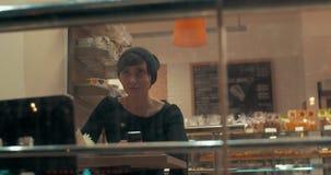 Νέα γυναίκα στο μήνυμα δακτυλογράφησης καφέδων σε κινητό με το ευτυχές βλέμμα φιλμ μικρού μήκους