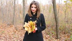Νέα γυναίκα στο μαύρο παλτό που κρατά μια ανθοδέσμη των φύλλων φθινοπώρου απόθεμα βίντεο