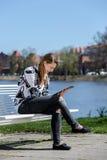 Νέα γυναίκα στο πάρκο με έναν υπολογιστή ταμπλετών Στοκ φωτογραφία με δικαίωμα ελεύθερης χρήσης