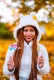 Νέα γυναίκα στο πάρκο την ηλιόλουστη ημέρα φθινοπώρου, που χαμογελά, κρατώντας τα φύλλα και την καραμέλα Εύθυμο όμορφο κορίτσι στ Στοκ Φωτογραφίες