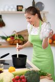 Νέα γυναίκα στο πράσινο μαγείρεμα ποδιών στην κουζίνα Η νοικοκυρά προετοιμάζει τη σούπα Στοκ Εικόνες