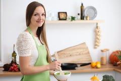Νέα γυναίκα στο πράσινο μαγείρεμα ποδιών στην κουζίνα Νοικοκυρά που τεμαχίζει τη φρέσκια σαλάτα στοκ εικόνες με δικαίωμα ελεύθερης χρήσης