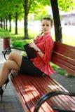 Νέα γυναίκα στο πράσινο πάρκο, με το σημειωματάριο και τη μάνδρα Στοκ εικόνες με δικαίωμα ελεύθερης χρήσης