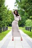 Νέα γυναίκα στο προκλητικό μακρύ γκρίζο φόρεμα στοκ φωτογραφία