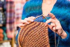 Νέα γυναίκα στο πλέξιμο του καταστήματος με την κυκλική βελόνα Στοκ εικόνα με δικαίωμα ελεύθερης χρήσης
