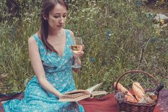 Νέα γυναίκα στο ρομαντικό μπλε φόρεμα σε ένα πικ-νίκ Το κορίτσι διαβάζει Στοκ Εικόνες