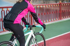 Νέα γυναίκα στο ρόδινο οδηγώντας οδικό ποδήλατο σακακιών στη γραμμή ποδηλάτων γεφυρών στην κρύα ηλιόλουστη ημέρα φθινοπώρου Υγιής στοκ φωτογραφία
