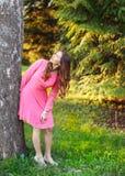 Νέα γυναίκα στο ρόδινο φόρεμα, που κλίνει στο δέντρο, που ανατρέχει, με τον ήλιο στοκ εικόνα