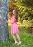 Νέα γυναίκα στο ρόδινο φόρεμα, που στέκεται δίπλα στο δέντρο, κλίση, looki στοκ φωτογραφίες