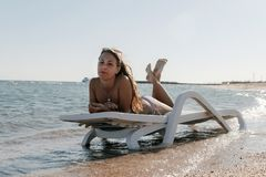 Νέα γυναίκα στο σαλόνι μονίππων στην παραλία θάλασσας Το κορίτσι χαλαρώνει στο bea Στοκ Εικόνες