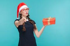 Νέα γυναίκα στο σκοτεινό φόρεμα και γυαλιά που κρατούν το κιβώτιο δώρων Στοκ εικόνες με δικαίωμα ελεύθερης χρήσης