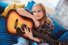 Νέα γυναίκα στο σπίτι στην κιθάρα εκμετάλλευσης χόμπι καθιστικών στοκ εικόνα