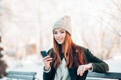 Νέα γυναίκα στο χειμερινό πάρκο που μιλά το κινητό τηλέφωνο Στοκ Εικόνα