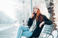 Νέα γυναίκα στο χειμερινό πάρκο που μιλά το κινητό τηλέφωνο Στοκ εικόνα με δικαίωμα ελεύθερης χρήσης