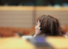 Νέα γυναίκα στο headser στη διάσκεψη Στοκ εικόνα με δικαίωμα ελεύθερης χρήσης