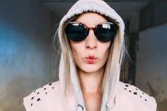 Νέα γυναίκα στο hoodie που κάνει τη έκφραση του προσώπου Στοκ φωτογραφία με δικαίωμα ελεύθερης χρήσης