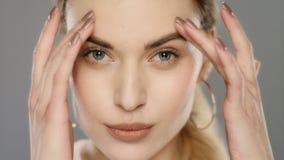 Νέα γυναίκα σχετικά με το δέρμα προσώπου στο στούντιο Πρότυπο μόδας που διορθώνει makeup απόθεμα βίντεο