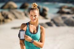 Νέα γυναίκα σχετικά με το smartphone armband Στοκ εικόνες με δικαίωμα ελεύθερης χρήσης