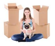 Νέα γυναίκα τα καφετιά κουτιά από χαρτόνι και το χαριτωμένο σκυλί μαλαγμένου πηλού που απομονώνονται με Στοκ φωτογραφία με δικαίωμα ελεύθερης χρήσης