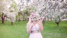 Νέα γυναίκα την άνοιξη σε ένα ανθισμένο πάρκο απόθεμα βίντεο
