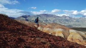 Νέα γυναίκα τουριστών με το σακίδιο πλάτης και καπέλο που προέρχεται κάτω από το κόκκινο βουνό πετρών Υπάρχει πλασματικό φυσικό τ απόθεμα βίντεο