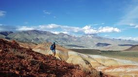 Νέα γυναίκα τουριστών με το σακίδιο πλάτης και καπέλο που προέρχεται κάτω από το κόκκινο βουνό πετρών Υπάρχει πλασματικό φυσικό τ φιλμ μικρού μήκους