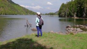 Νέα γυναίκα τουριστών που εξετάζει την όμορφη λίμνη βουνών στο ισπανικό εθνικό πάρκο Augestortes φιλμ μικρού μήκους