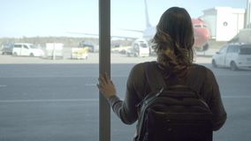 Νέα γυναίκα τουριστών στον αερολιμένα, που εξετάζει μέσω του παραθύρου το αεροπλάνο φιλμ μικρού μήκους