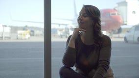 Νέα γυναίκα τουριστών στον αερολιμένα, που εξετάζει μέσω του παραθύρου το αεροπλάνο απόθεμα βίντεο