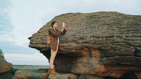 Νέα γυναίκα τουριστών backpacker που φωτογραφίζει το τοπίο στη κάμερα smartphone της μετά από στο βράχο στο ηλιοβασίλεμα Στοκ εικόνα με δικαίωμα ελεύθερης χρήσης
