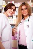 Νέα γυναίκα φαρμακοποιών δύο πίσω από το γραφείο Στοκ Φωτογραφίες